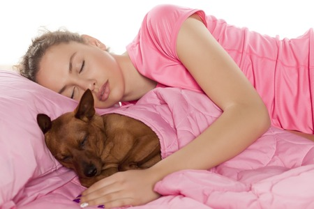 beautiful girl sleeping with her little dog in her bed