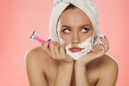 disappointed young woman with foam on the face and a razor in her hand Stock Photo
