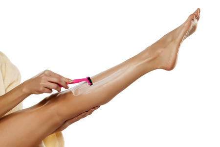 young woman shaving her legs with razor