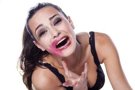 beautiful desperate girl with smeared makeup posing on white