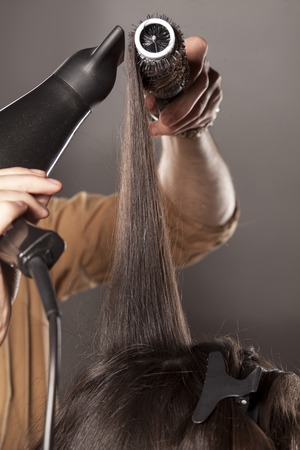 hairdresser doing his client hair with a hair drier and comb Stock Photo