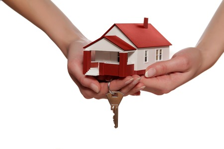 Miniature model house and key in womans hands Stock Photo