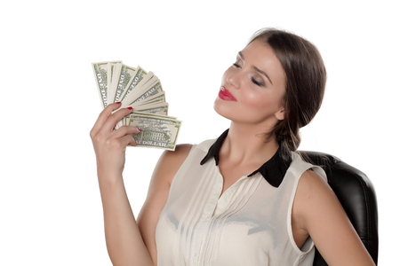 young business woman uses money as a fan
