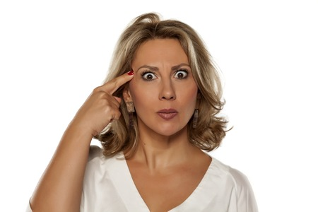beautiful middle-aged woman with a questionable gesture and her finger to her forehead Stock Photo