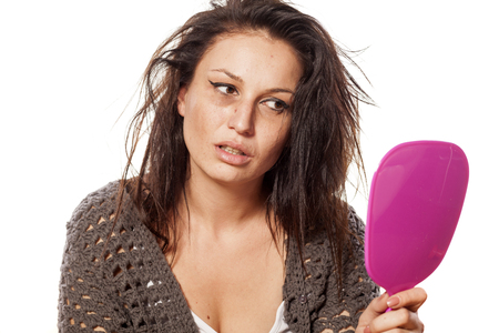 uncared messy woman looking at herself in the mirror Stock Photo