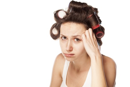 unhappy and worried young woman with hair curlers Stock Photo