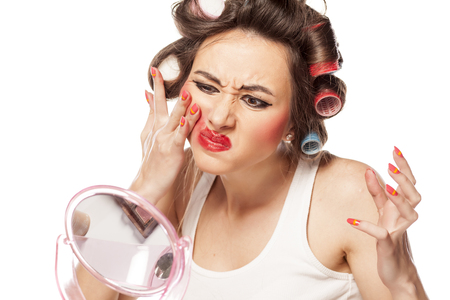 nervous woman with curlers removes makeup with her hands Stock Photo