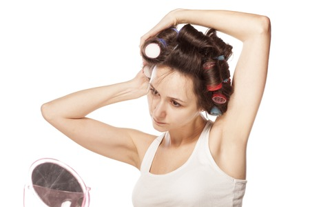 concentrated woman without make-up curls her hair with curlers