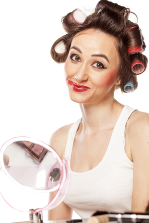 smiling woman with curlers posing with smeared makeup