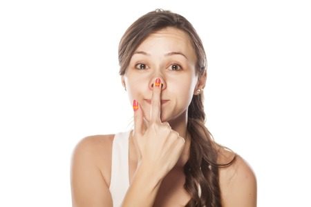 Funny young woman lifted her nose with a finger