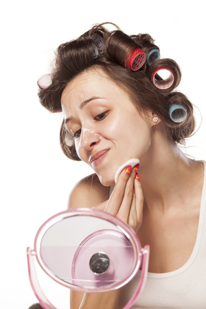 woman with curlers clean her face with cream and cotton pad