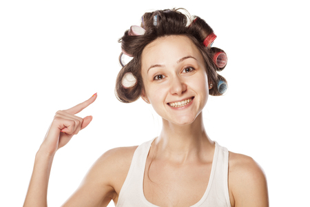 smiling woman showing with her ??finger in her curlers