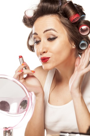satisfied woman with bad makeup looking herself in the mirror