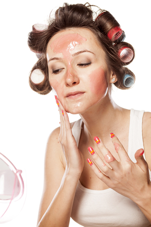 hair roller: calm young woman with curlers applying face mask