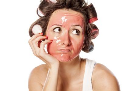 portrét znuděné mladé ženy s natáčky a masku na obličej
