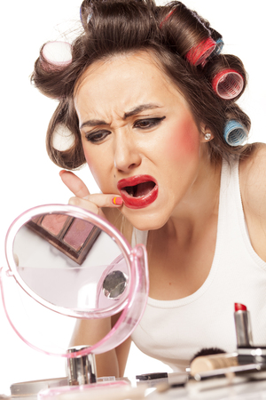 smeared: dissatisfied unhappy woman with curlers and with smeared makeup Stock Photo
