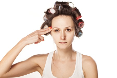 unhappy woman with hair curlers make suicidal gesture Stock Photo