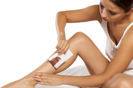 depilate: woman waxing her legs using tape and wax for depilation Stock Photo