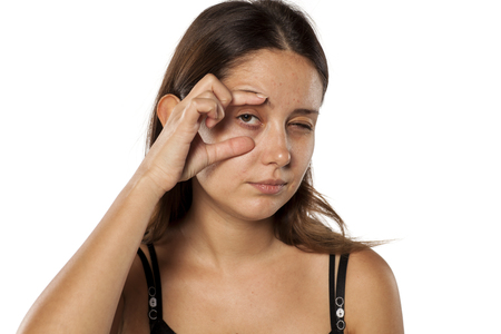 young beautiful woman opens her eye with her fingers Stock Photo