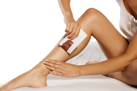 woman waxing her legs using tape and wax for depilation Stock Photo