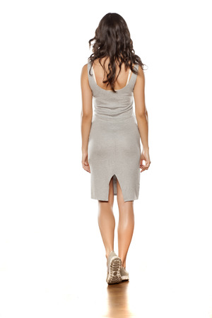 back view of a young beautiful woman posing in a short dress and espadrille