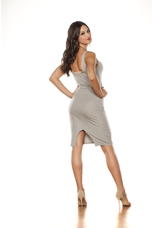 back view of a young pretty woman standing in a short dress and high heels Stock Photo