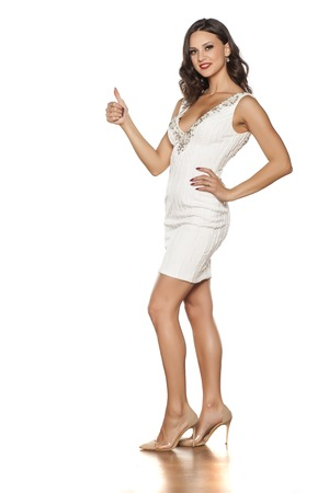 smiling young beautiful woman in elegant short dress and high heels showing thumbs up Stock Photo