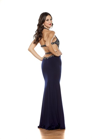 blue dress: back view of a young woman posing in a long blue dress on a white background