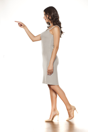 profile of a young beautiful woman in a short dress and high heels pointing on white