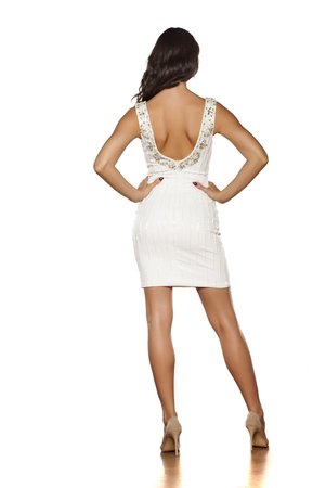 Back view of a young beautiful woman posing in a white short dress and high heels