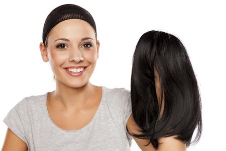 jeune femme avec un chapeau de perruque sur sa tête tenant une perruque dans la main