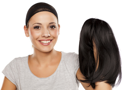 young woman with a wig cap on her head holding a wig in hand