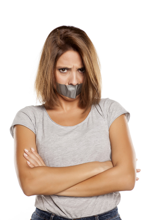 sellotape: angry young woman with adhesive tape over her mouth
