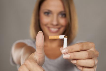 junge glückliche Frau, die eine gebrochene Zigarette hält und Daumen zeigt Standard-Bild