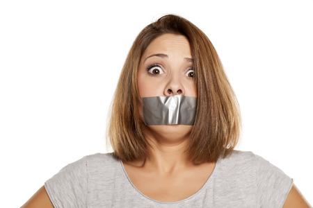 bang jonge vrouw met plakband voor haar mond Stockfoto