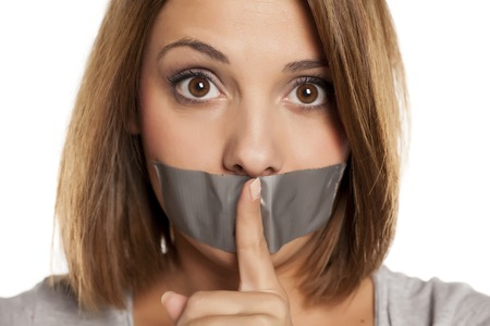angry young woman with adhesive tape over her mouth, and finger in front of the tape Stock Photo