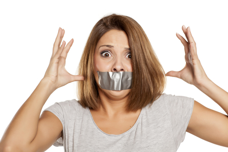 silenced: nervous young woman with adhesive tape over her mouth Stock Photo