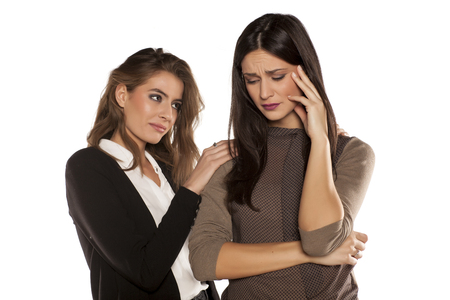 sympathize: a young woman comforting her crying friend Stock Photo