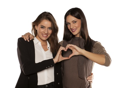 two embraced women make heart shape with her hands Stock Photo