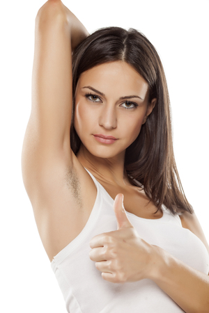 underarms: young woman shows her unshaved armpit and showing thumbs up Stock Photo