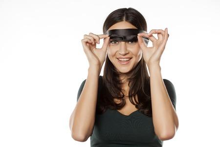 행복한 여자가 눈가리개를 벗다.