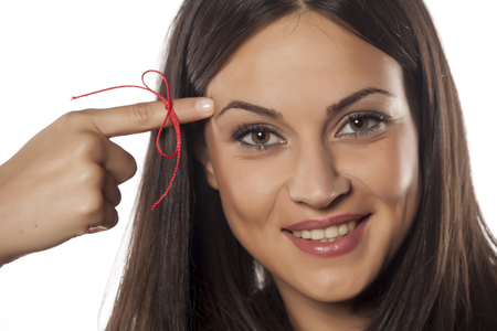 forgetful young woman with a finger tied with a red rope