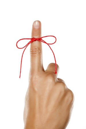 index finger tied with a red rope Stock Photo
