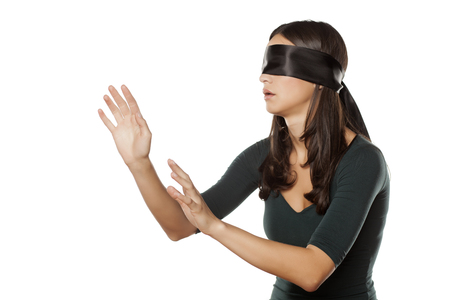 lost blindfolded woman on a white background Stock Photo
