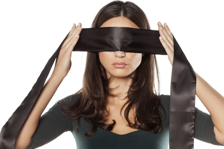 serious woman adjusts blindfold over her eyes