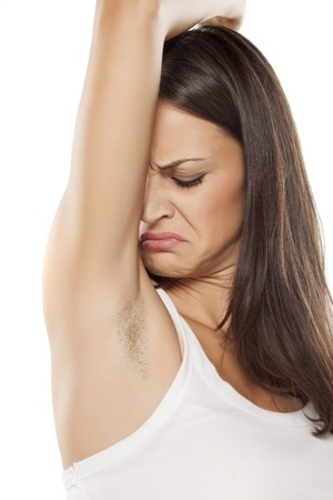 young woman smells her unshaved armpit