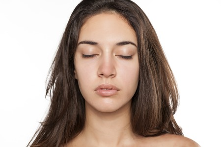 portrait of a girl with no makeup with closed eyes on white background