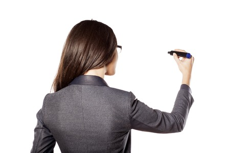 back view of businesswoman writing with a marker