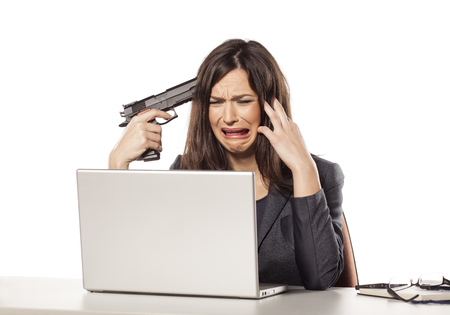 holding gun to head: weeping young businesswoman wants to kill herself with a gun Stock Photo