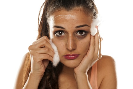 young beautiful woman remove her make-up with cotton pad